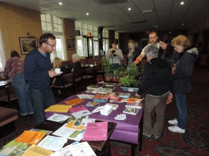 Leaflets and books and plants on the table. Local people chatting and getting to know each other.
